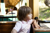 Portrait of little boy sitting in cafe and looking away — Stock Photo