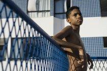 Poitrine nue adolescent garçon appuyé sur la clôture dans la lumière du soleil — Photo de stock