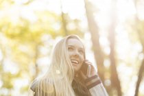 Smiling teenage girl on cell phone in autumn — Stock Photo