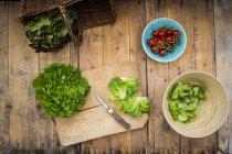 Подготовка салата, помидоров, салановой на рубке доски, ножа — стоковое фото