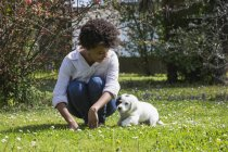 Женщина играет с собакой на лугу — стоковое фото