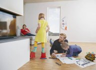 Father and son drawing on floor while mother and daughter having fun at home — Stock Photo