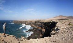 Espanha, Ilhas Canárias, Fuerteventura, alpinista de pé sobre o penhasco e olhando a vista — Fotografia de Stock