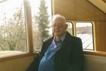 Senior man sitting in cable railway — Stock Photo