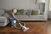 Toddler vacuuming a wooden floor in the living room — Stock Photo