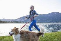 Adolescente d'Italie, Lecco, courir avec son chien au bord lac — Photo de stock