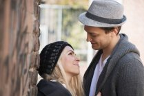 Young couple standing face to face by the brick wall — Stock Photo