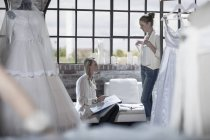 Designer and bride to be discussing wedding dress in fashion studio — Stock Photo
