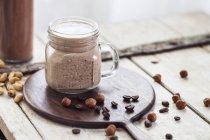 Bicchiere di frullato con chicchi di caffè, nocciole tostate e semi di chia — Foto stock