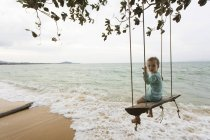 Jovem na praia, sentada no balanço na Tailândia — Fotografia de Stock