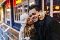 Young woman kissing her boyfriend — Stock Photo