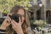 Улыбающаяся молодая женщина фотографирует — стоковое фото