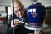 Senior woman dekorieren Keramikvase in seiner Freizeit — Stockfoto