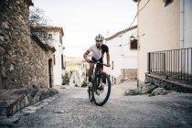 Mountain biker riding uphill in mountain village — Stock Photo