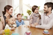 Happy family of five sitting at table at home — Stock Photo