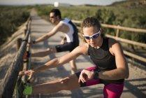 Donna allegra con smartwatch e uomo che allunga su un ponte — Foto stock