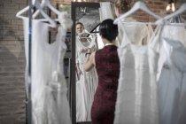 Vestido de noiva designer e noiva para estar na loja nupcial — Fotografia de Stock
