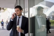 Businessman leaning on windowpane with cell phone — Stock Photo