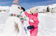 Cute caucasian girl building snowmen in winter — Stock Photo
