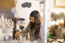 Young woman working in her own little cafe — Stock Photo
