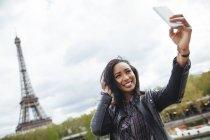 França, Paris, Jovem mulher tomando selfie telefone inteligente na frente da Torre Eiffel — Fotografia de Stock
