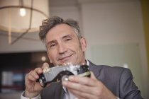 Mature man playing with classic car model — Stock Photo