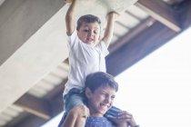 Niño, sentado sobre los hombros del hermano en casa - foto de stock