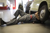 Car mechanic on creeper dolly working in repair garage — Stock Photo