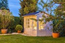 Vertente do jardim iluminado com vasos de plantas e árvores — Fotografia de Stock