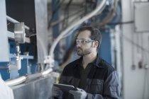 Jeune technicien travaillant avec tablette pc — Photo de stock