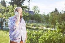 Giovane con smartphone in giardino, telefonare — Foto stock