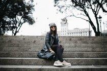 Усміхаючись молода жінка, сидячи на сходах — стокове фото