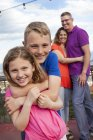 Portrait of boy hugging his little sister while their parents standing in the background — Stock Photo