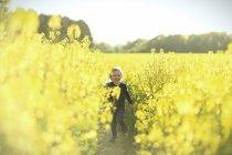 Fille heureuse en cours d'exécution dans le champ de canola — Photo de stock