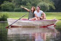 Young couple sitting in a rowing boat on lake looking at distance — Stock Photo