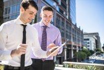 Zwei lächelnde Geschäftsleute im Freien, die auf Tablets schauen — Stockfoto