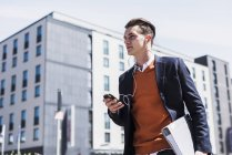 Young man with cell phone, earbuds and folder on the move — Stock Photo