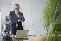 Successful businessman standing in board room using laptop — Stock Photo