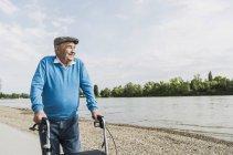 Hombre senior sonriente caminando con andador con ruedas en riverside - foto de stock