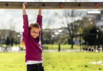 Smiling little girl hanging on climbing frame on playground — Stock Photo