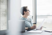 Businesswoman at desk in office thinking — Stock Photo