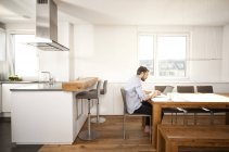 Man sitting at table in his open plan kitchen using laptop — Stock Photo