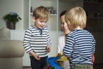 Mère et deux petits garçons jouant à la maison avec des jouets — Photo de stock