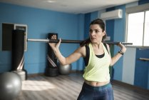 Mature woman training with fitness bar in gym — Stock Photo