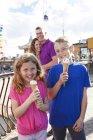 Retrato de irmão e irmã com casquinhas de sorvete e os pais no fundo — Fotografia de Stock