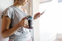 Young woman with healthy drink looking at cell phone — Stock Photo