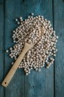 Dried chickpeas and wooden spoon on wood — Stock Photo