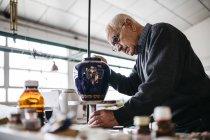 Старший чоловік лицювальні керамічні вази у вільний час — стокове фото
