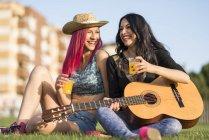 Amigos sentados en la hierba, tocar la guitarra - foto de stock