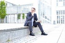 Empresário sentado com tablet digital — Fotografia de Stock